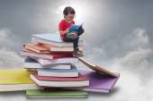 Boy playing tablet and sitting on pile of books — Stock Photo
