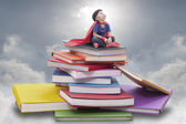 Superhero boy child sitting on pile of books — Stock Photo