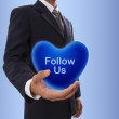Businessman hand holding blue heart bubble with follow us word — Stock Photo #61258161