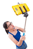 Happy woman taking picture with smartphone selfie stick — Stock Photo