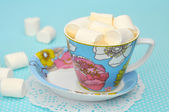 Coffee with marshmallows in a blue cup on a paper napkin — Stock Photo