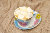 Coffee with marshmallows in a blue cup on a knitted woolen scarf — Stock Photo