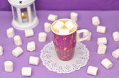 Coffee with marshmallows in a purple mug on a purple background. — Stock Photo