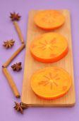Fette di cachi Sharon su una tavola di legno, anice stellato e cinnam — Foto Stock
