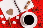 Cup of coffee and note pad on red textile background. — Stock Photo