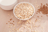 Oatmeal in a white bowl on wooden background. — Stock Photo