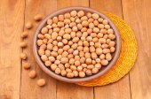 Hazelnuts on a plate and orange napkin on wooden background — Stock Photo