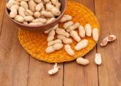Peanuts in a clay bowl on a wicker orange place mat — Stock Photo