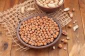 Hazelnuts and peanuts in a clay bowls on a wooden background — Stock Photo
