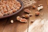 Hazelnut and peanut pods on wooden background — Stock Photo