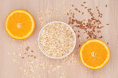 Oatmeal in a white bowl and halved oranges  — Stock Photo