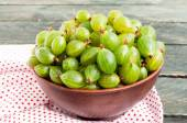 Fresh green gooseberries in a ceramic bowl on a napkin textile. — Stock Photo