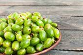 Fresh wet gooseberries on a plate on a wooden background. Green — Stock Photo