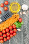 Cherry tomatoes, pasta, olive oil, garlic, herbs and pasta tongs — Stock Photo