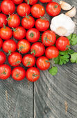Cherry tomatoes, garlic and herbs on a wooden background. Vegeta — Stock Photo