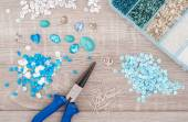 Crystals, pendants, charms, plier, glass hearts, box with beads — Stock Photo