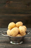 Organic young potato in a bowl on a wooden table. Selective focu — Stock Photo