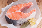Raw salmon steak red fish and spices on wooden table — Stock Photo