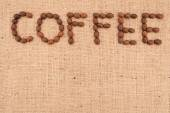 The word coffee made from coffee beans on burlap background — Stock Photo
