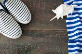 Shoes and striped cloth on old wooden background — Stock Photo