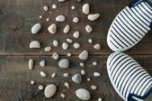 Shoes and stones on old wooden background — Stock Photo
