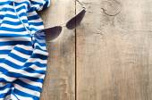 Summer sea-striped cloth and sunglasses on wooden background — Stock Photo