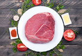 Raw meat beef with herbs, spices, olive oil and tomatoes on old — Stock Photo