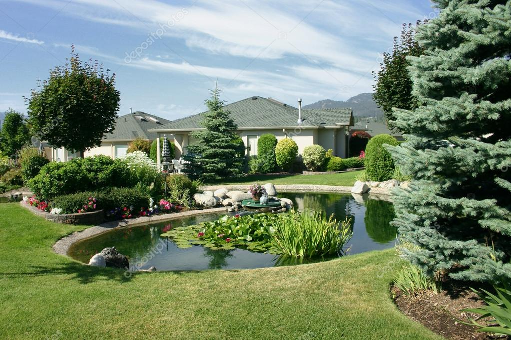 Beautiful landscaping with pond between single family for Home and garden landscaping pictures