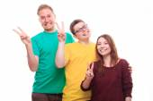 Three young people showing victory sign and smiling  — Stock Photo
