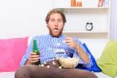 Surprised man eating popcorn on the sofa — Stock Photo