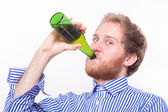 Young man drinking a bottle of beer — ストック写真