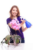 Pretty girl watering orchid flower with spray — Stock Photo