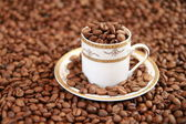 Coffee cup full of coffee beans — Stock Photo
