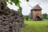 Wooden mill and braided fence in the countryside — Stock fotografie
