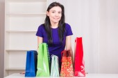 Smiling happy girl prepares bags gifts for Christmas — Zdjęcie stockowe