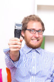 Happy bearded man with an electric razor — Stock Photo