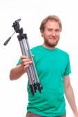 Bearded happy man holding a tripod — Stock Photo