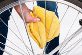 Cleaning bicycle spokes in the wheel with a cloth — Stock Photo