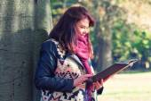 Young woman rests against a tree and reading a book in the park — Stock Photo