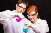 Two chemists holding a test tube in a lab — Stock Photo