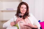 Woman on the sofa pointing a glass of wine — Stock Photo