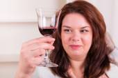 Plump and cheerful woman holding a glass of wine — Stock Photo