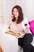 Plump woman at home eating chocolates and drinking wine — Photo