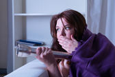 Frightened woman in bed with a torch at night — Stock Photo