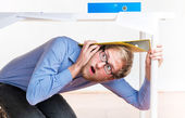 Employee hiding under a desk during an earthquake — Stock Photo