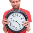 Sad bearded man holding big clock on white  — Stockfoto #63709691