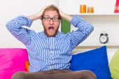 Shocked man screams in horror and sitting on the sofa — Stock Photo