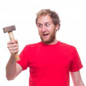 Surprised man holding hammer — Stock Photo