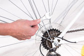 Woman hand repairing bicycle — Stock Photo