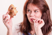Plump woman eating donut — Stock Photo
